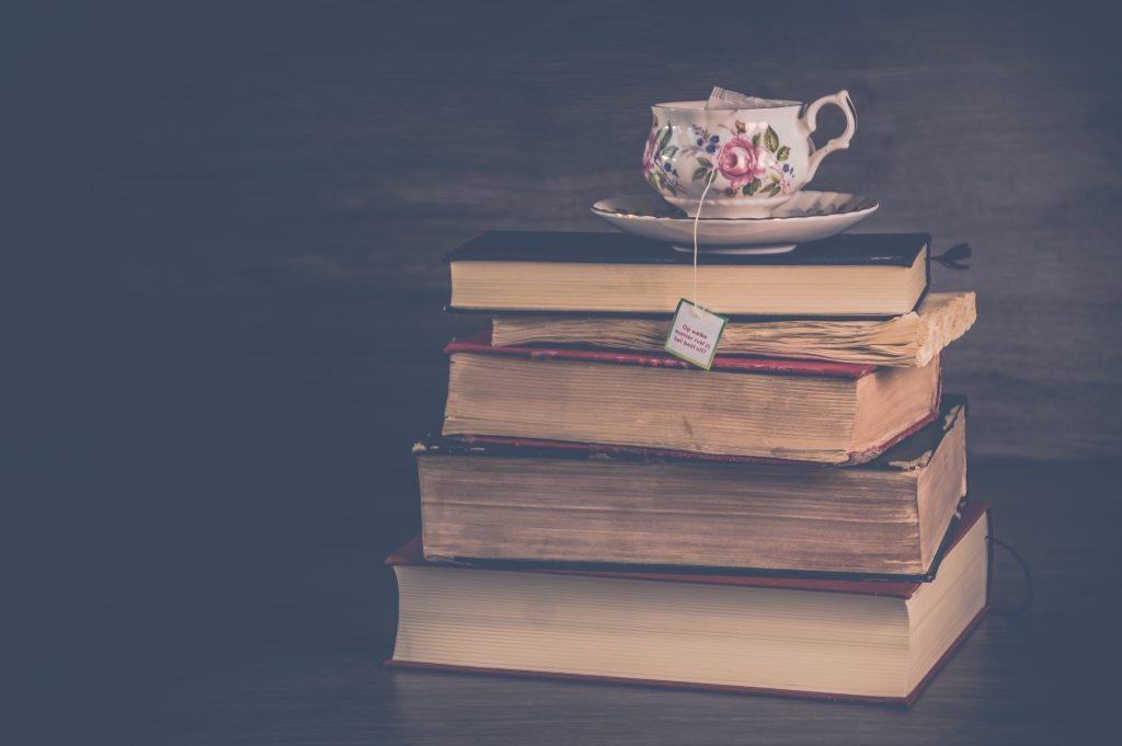 a pale of books, spine in, with a delicate floral tea cup balanced on top